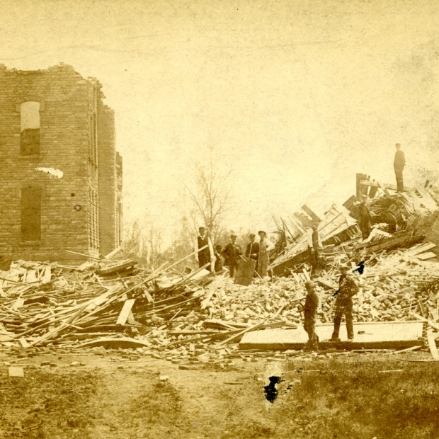 Two men survey destroyed buildings