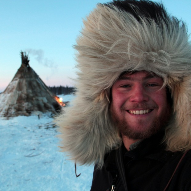 Alex Reich in the Arctic in a fur hood with a teepee structure in the background