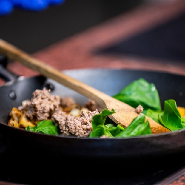 A small saute pan with fresh spinach leaves and ground meat, ready to be tossed together