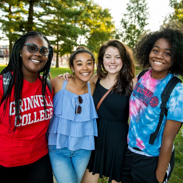Four women stand together at NSO campus picnic