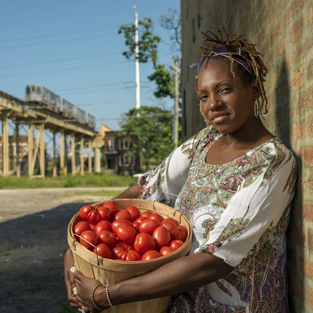 LaDonna Redmond holds a bushel of tomatoes