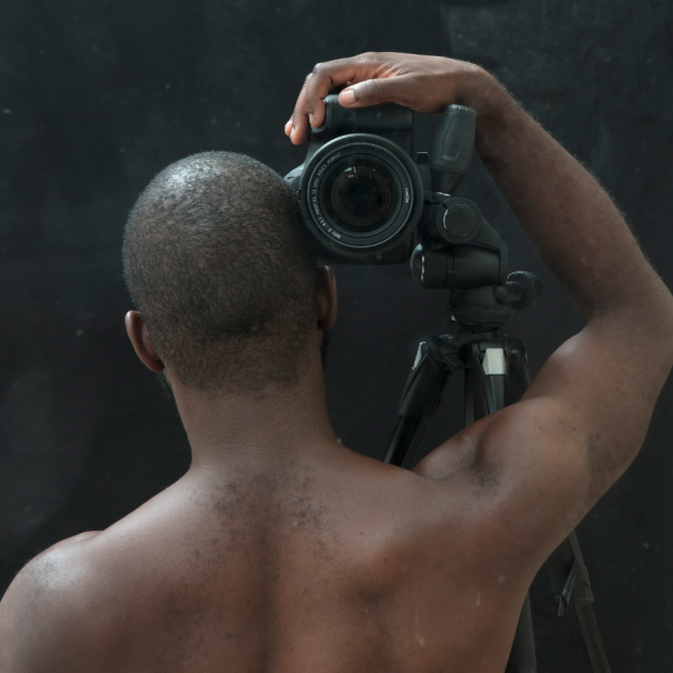View of a Black figure from behind with a camera perched on his shoulder aimed at the viewer.