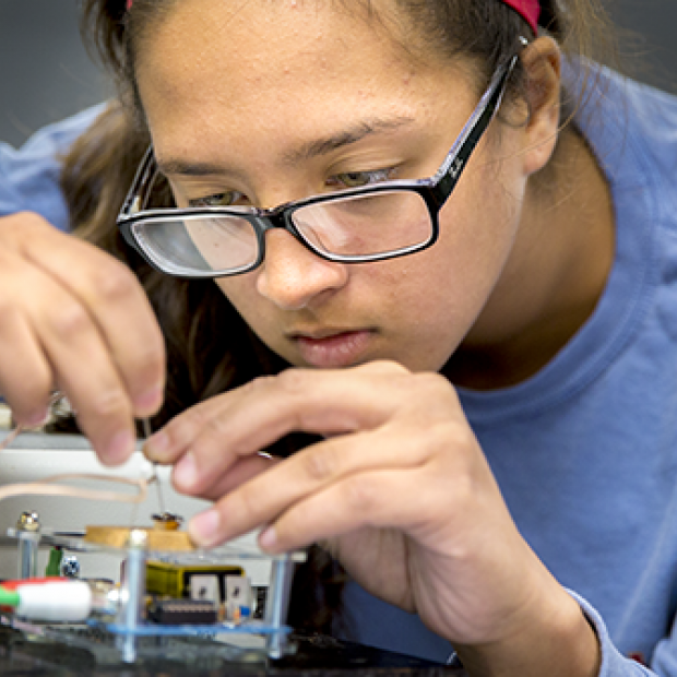 A student works with circuitry in a Grinnell Science Project lab