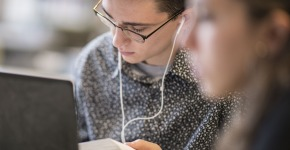 Student studying in Burling library with ear buds in