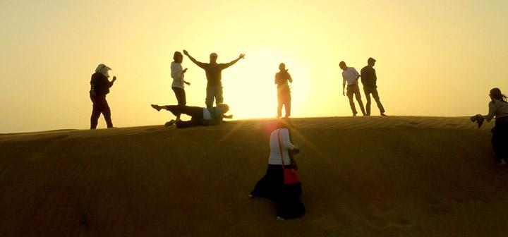 Group posing at top of dune with sun setting behind them