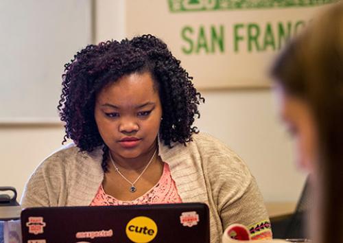 Two student sit at computers at an internship