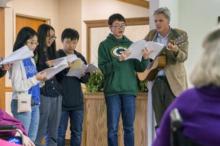 A group of students, accompanied by John Rommereim on guitar, perform for Mayflower residents.