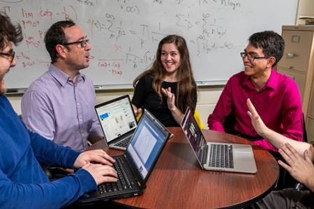 A professor and three students sit at a table with three open laptop computers