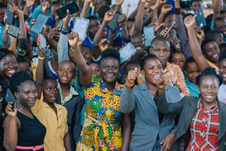 Angela Frimpong and students hold up digital devices