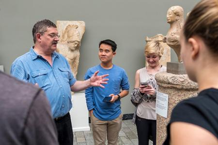 A professor and students study the statues at a Copenhagen museum