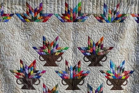 Mutlicolor quilt with basket motifs on cream background, quilted throughout