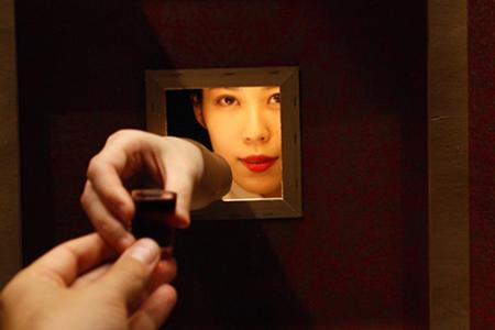 A woman hands a small glass of wine through a small square opening in a wall