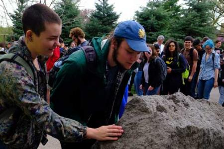 Two students with backpacks inspect the peace rock while crowd waits behind them