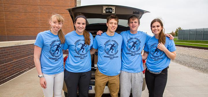 5 students stand next to a car loaded with donations for hurricane relief