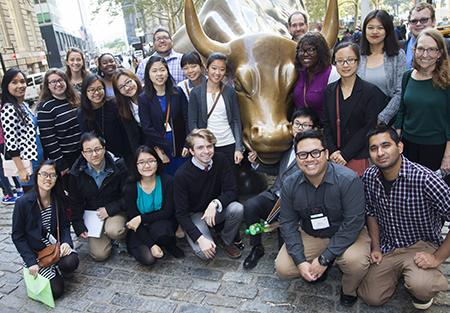 Jarren Santos and other students on a fall break tour to New York City pose in front of the Wall Street bull.