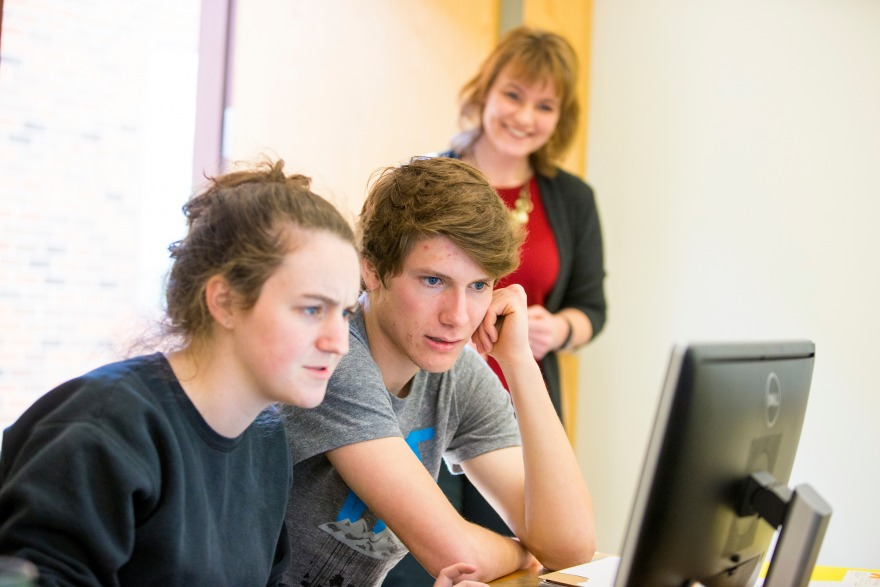 Two students work at a computer together while Professor Shonda Kuiper observes