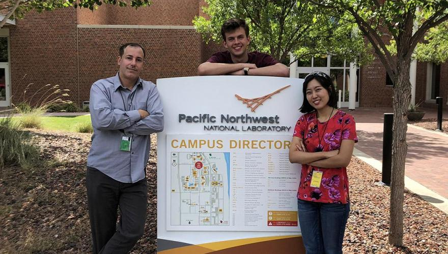 Two research students with their faculty mentor, Prof. Hernandez, leaning on a campus sign at the Pacific Northwest National Laboratory.