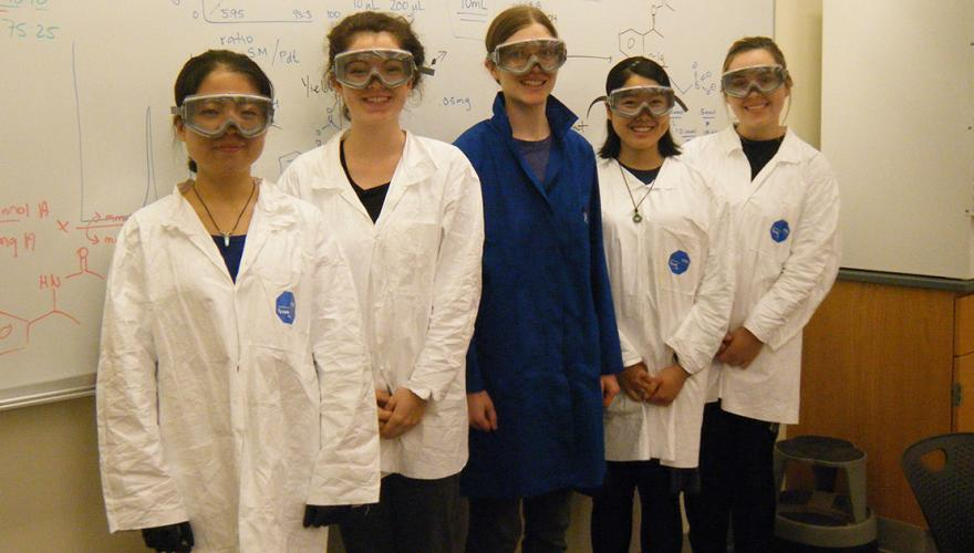 Four research students with their faculty mentor, Prof. Key, wearing lab coats and safety goggles in front of a markerboard showing chemical reactions