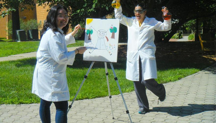 A research student with their faculty mentor, Prof. Ortiz, wear lab coats and hold glass flasks.