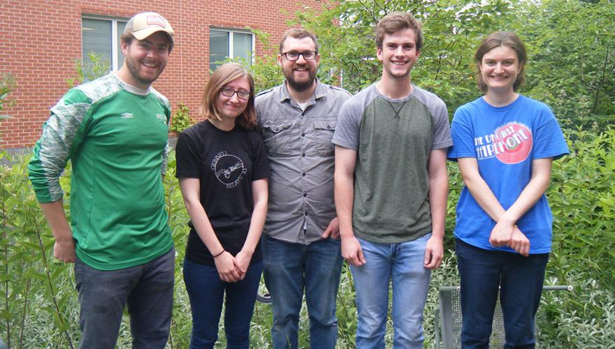 Four students and their faculty mentor outside the science building.
