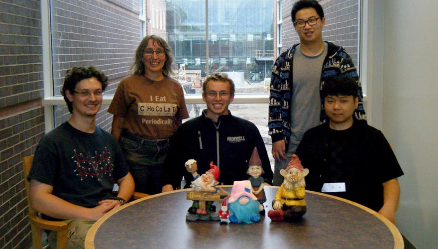 Four students and their faculty mentor pose with some gnome statues.