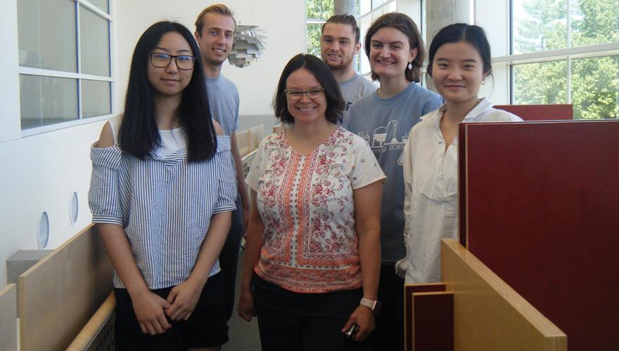 Five students and their faculty mentor among the study carrels in the science library.
