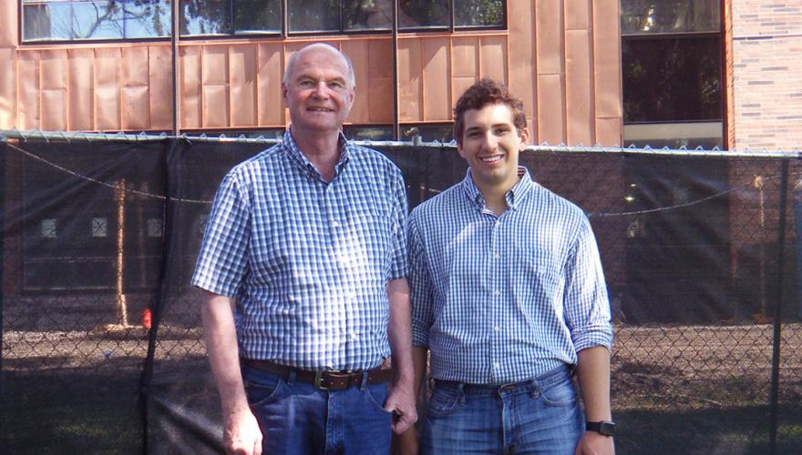 A student and his faculty mentor stand in front of the copper facade of a building.