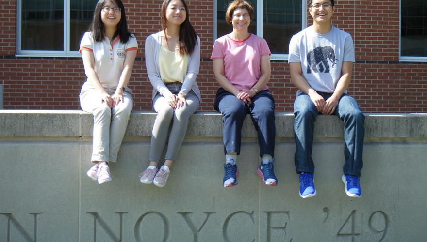 Three students and their faculty mentor sit on a low wall.