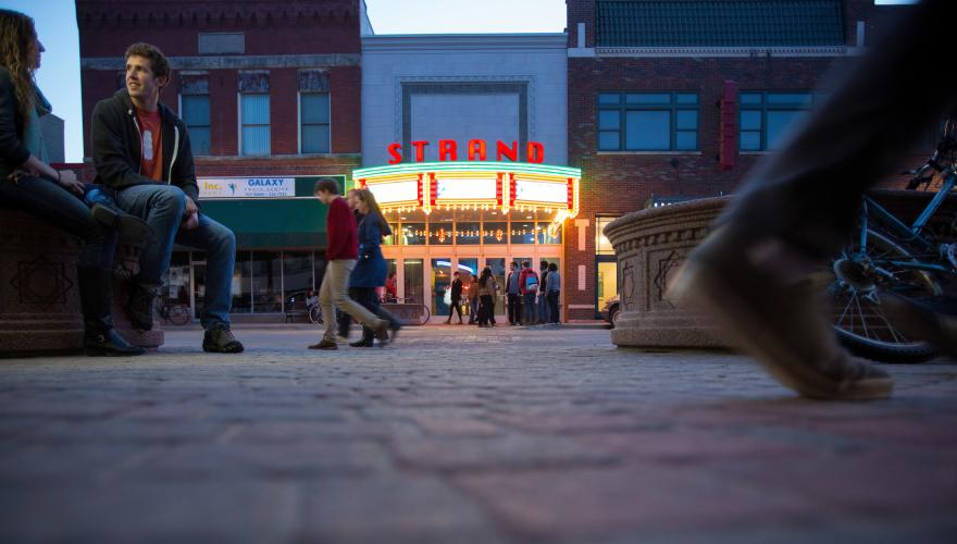people walk in the street in front of Strand Theater at night