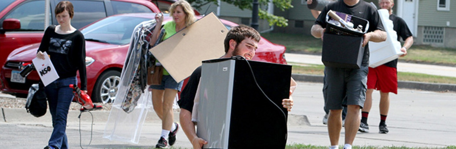 Family members help students carry belongings to a residence hall.