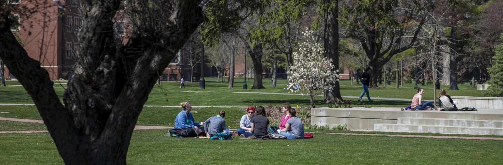 A group of students sits in the grass in central campus