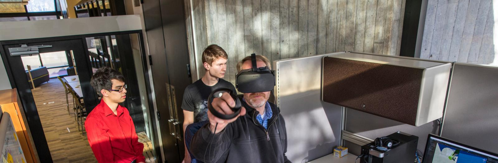 professor and students test virtual reality equipment