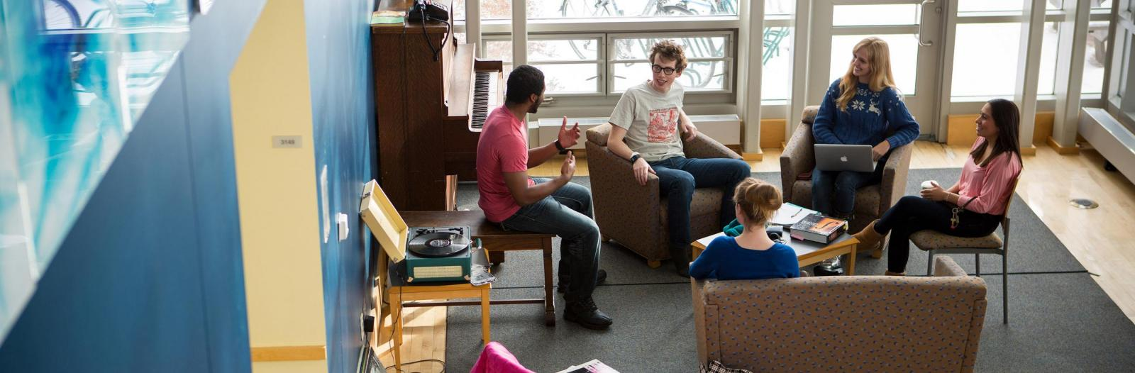 Students sit in chairs in an East Campus dorm foyer