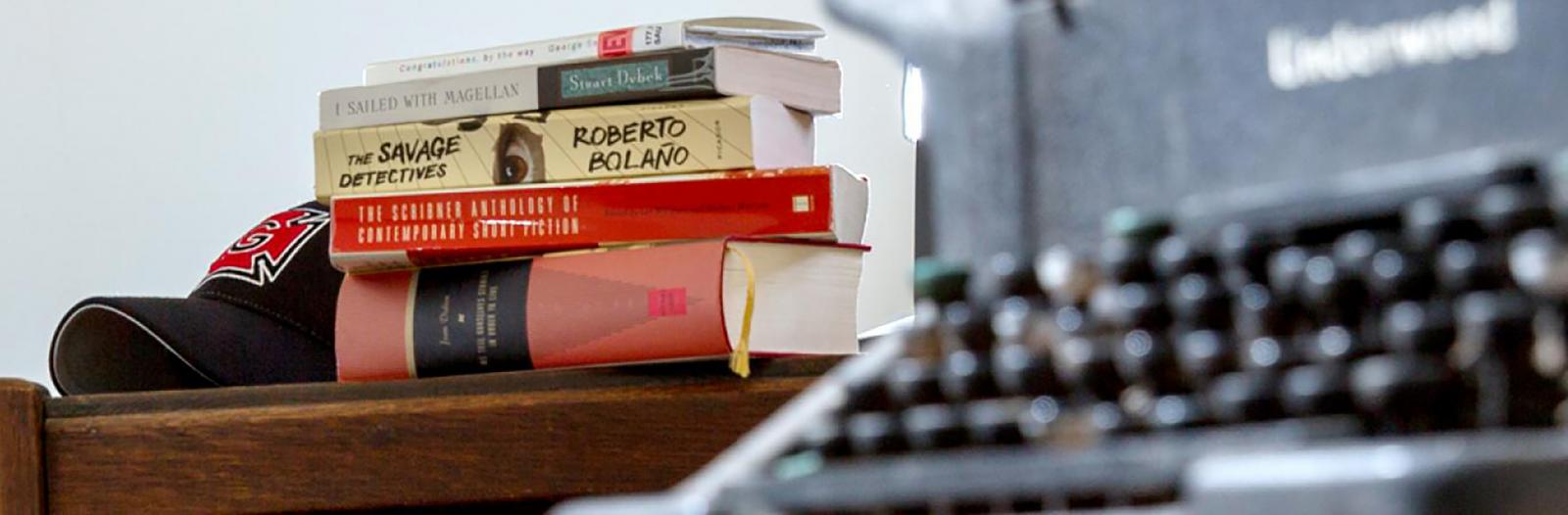 books on a table beside a typewriter
