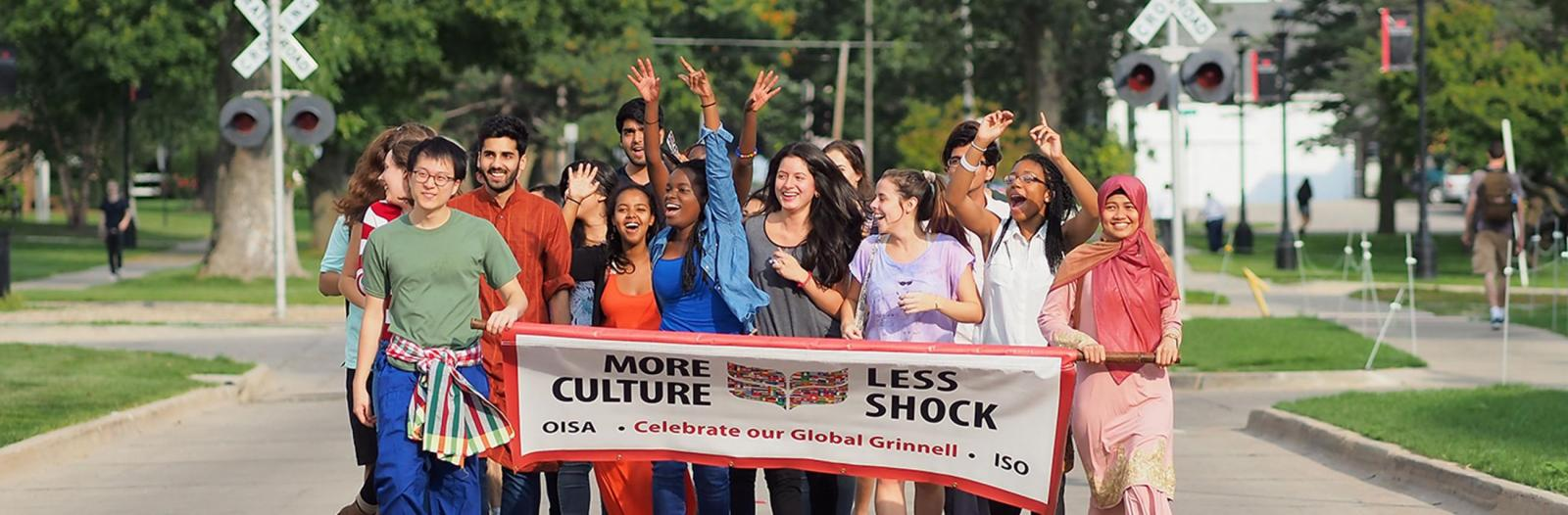diverse students holding banner that says more culture, less shock, celebrate our global Grinnell, OISA, ISO
