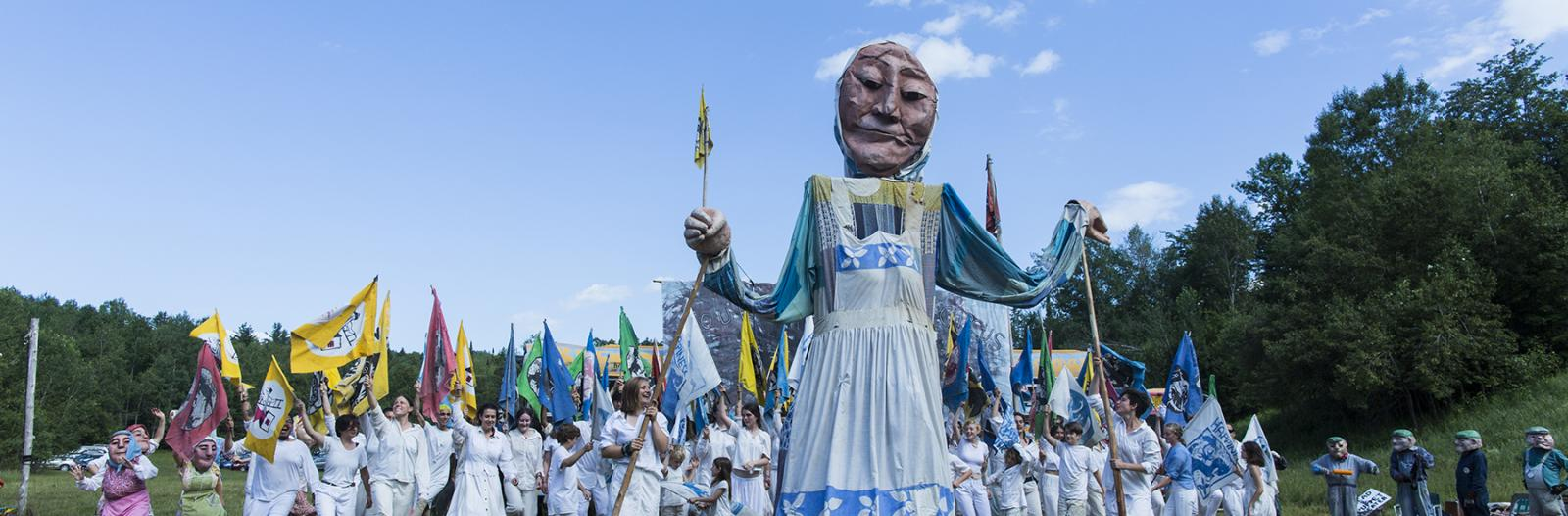 Large puppet leads crowd in scene from Bread and Puppet's The Grasshopper Rebellion