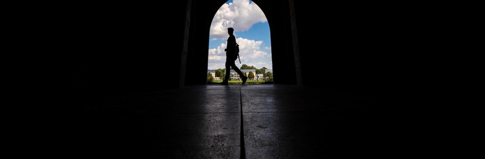 Silhouette of student walking in loggia archway