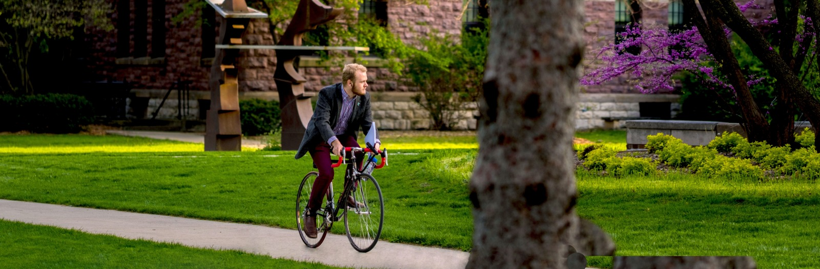 Student bikes past campus sculpture near Goodnow Hall on a beautiful spring day