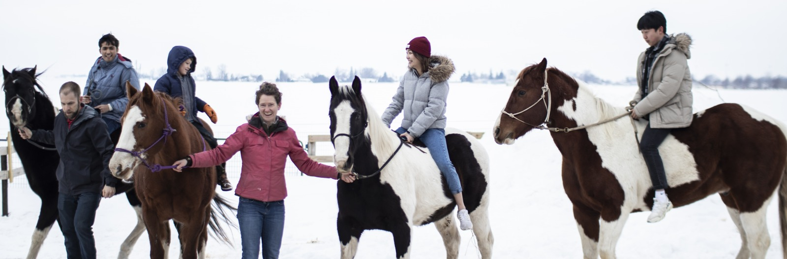 Students riding horses that are lead by adults