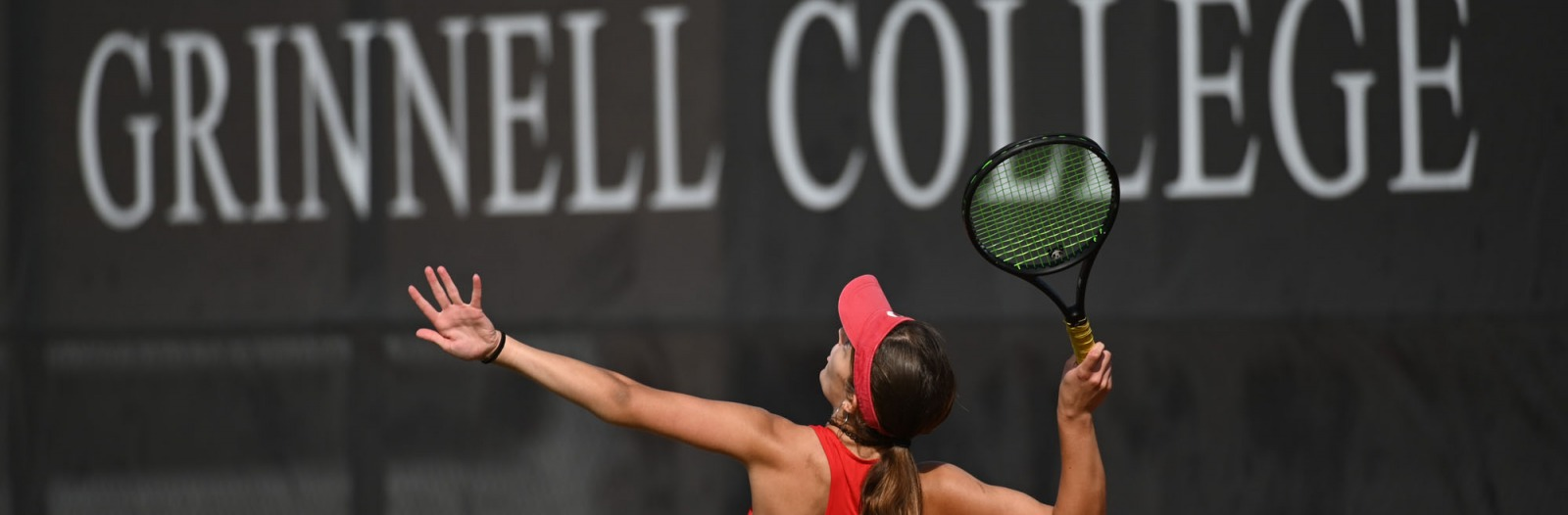 tennis player serves in front of 'Grinnell College' sign