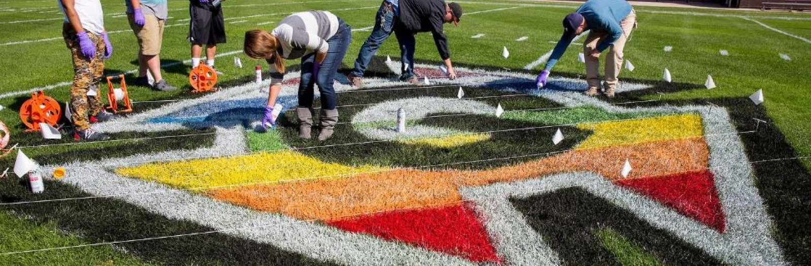 Students painting the football field with the Pride Honor G