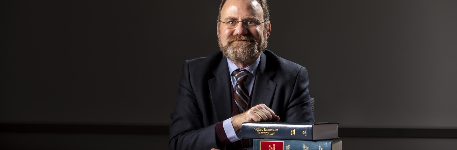 Doug Hess in a classroom at a table with large books