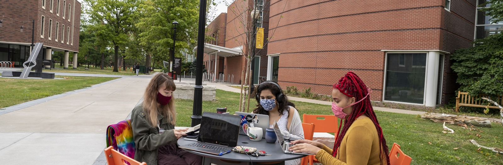 Three students wearing masks sit outside to study together
