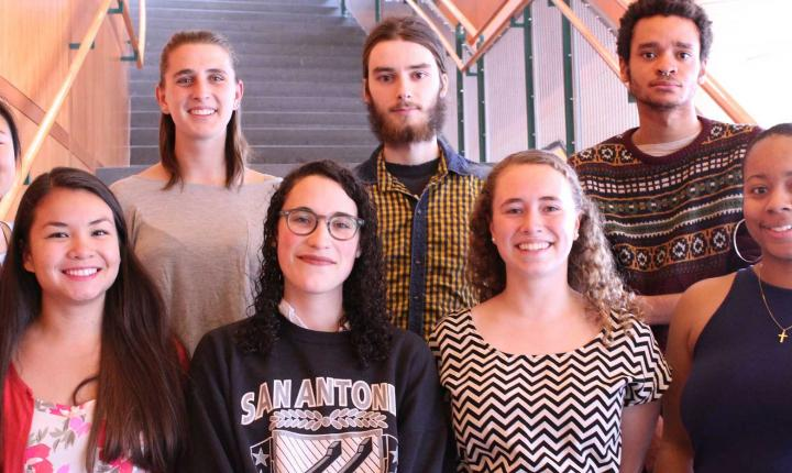 Group of smiling Grinnell Fulbright Grant winners posed on stairwell.