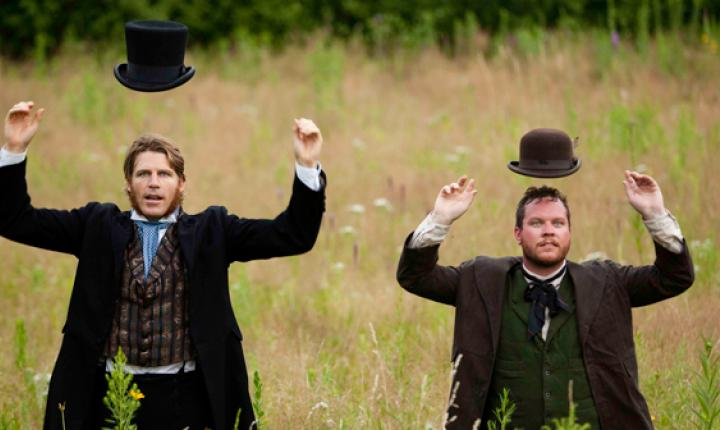 Two men in old fashioned clothes and hats flipped up above their heads walk through a meadow