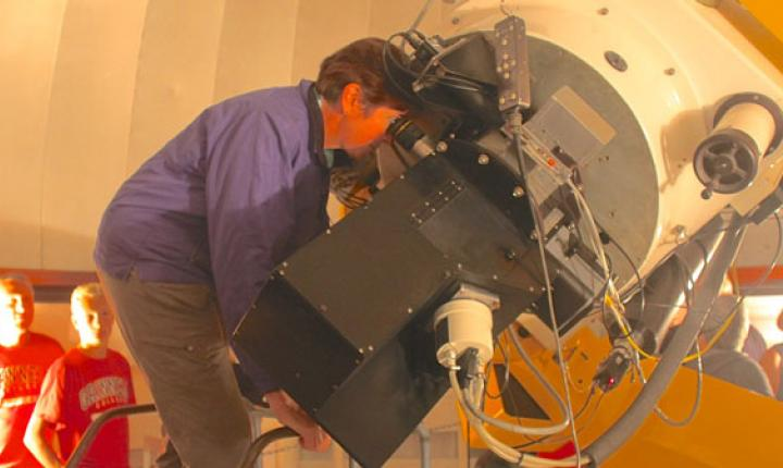 Person peers into large telescope while other look on