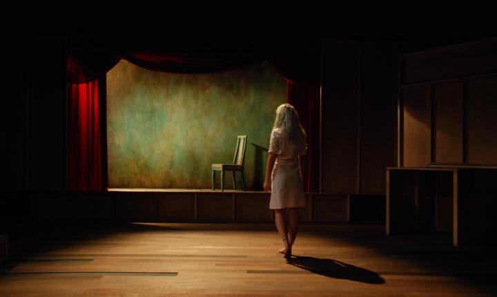 Single actor walks towards chair
