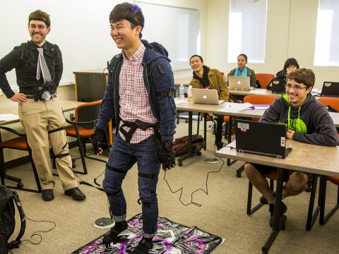 A student plays Dance Dance Revolution in a motion capture suit