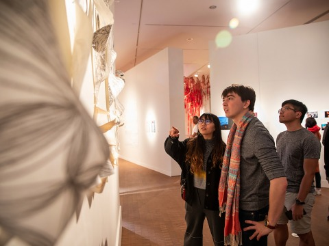 Students examine artwork at BAX