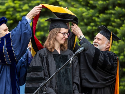 Kristin DeMoss receiving regalia in honorary degree ceremony